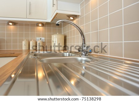Modern kitchen sink with mixer tap - stock photo