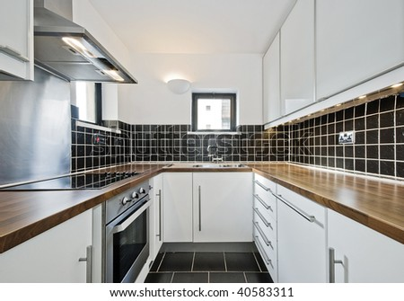 modern kitchen with black ceramic tiles and wooden worktop - stock photo