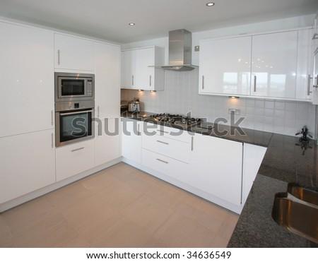 Modern kitchen with black granite worktop - stock photo