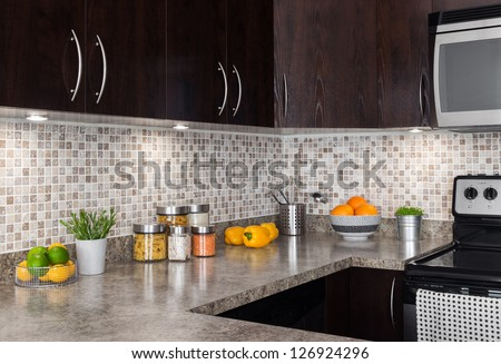 Modern kitchen with cozy lighting, and food ingredients on the counter top. - stock photo