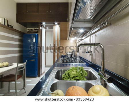 modern kitchen with faucet in the foreground and vegetable in the sink and blue refrigerators - stock photo