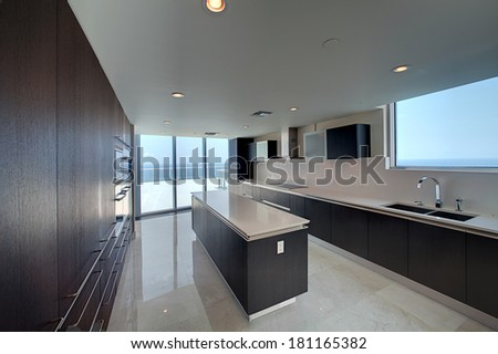 Modern kitchen with ocean view in penthouse and marble flooring  - stock photo