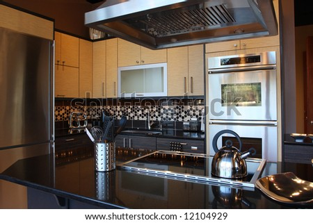 Modern Kitchen with stainless steel appliances and beautiful granite counters and tile back splash. - stock photo