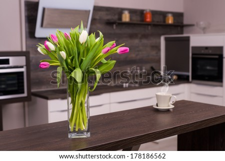 Modern kitchen with tulips and hot coffee. - stock photo