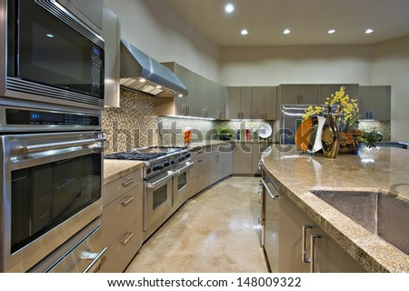 Modern kitchen with vent hood above stainless steel stove - stock photo