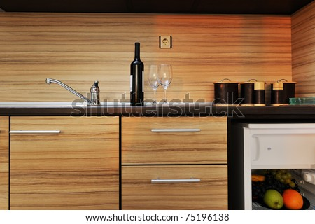 Modern kitchen wooden furniture with sink, blender and fridge - stock photo
