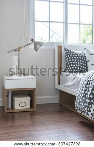 modern lamp on bedside table with wooden bed in modern bedroom - stock photo