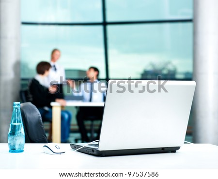 Modern laptop on foreground at empty workplace. Team of young businesspeople discussing plans on background - stock photo