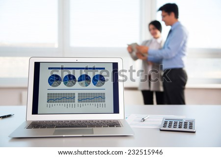 Modern laptop on foreground at empty workplace. Young businesspeople discussing plans on background - stock photo