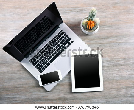 Modern laptop, smart phone and tablet with cactus on a wooden table - stock photo