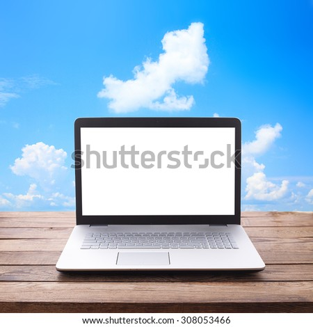 Modern laptop with a white screen on wooden table workplace. Mock up for design. Top view - stock photo