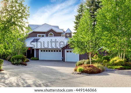 Modern large house exterior with curb appeal. View of garage and concrete floor driveway - stock photo