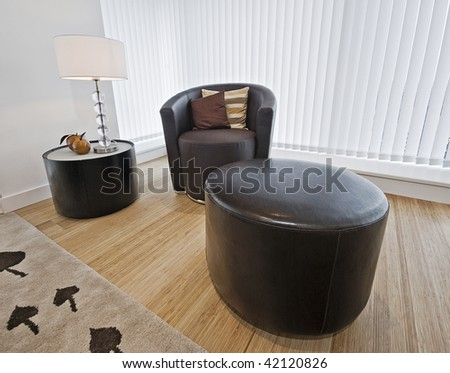 modern leather armchair with side table and reading lamp - stock photo