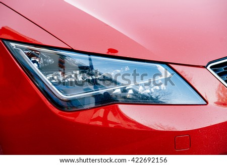 modern LED headlight of a red sport car - stock photo