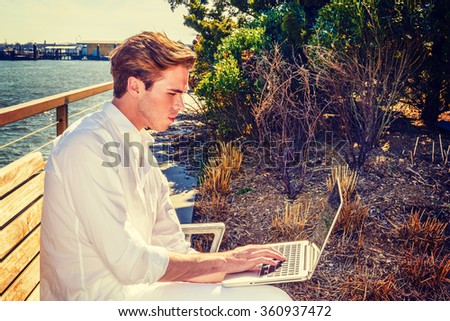 Modern life. American college student traveling, studying in New York, wearing white shirt, sitting at park by river, reading, typing, working on laptop computer. Side view. Instagram filtered effect. - stock photo