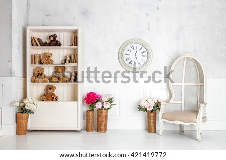 Modern light room interior with wardrobe, armchair and clocks on the wall. Kids room interior