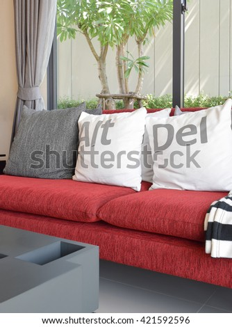 modern living room design with white pillows on the red sofa