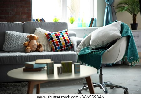 Modern living room interior in grey tones with bright blue plaid on chair - stock photo