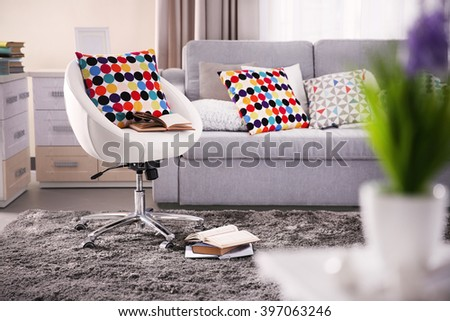 Modern living room interior in grey tones with colourful pillow on chair - stock photo