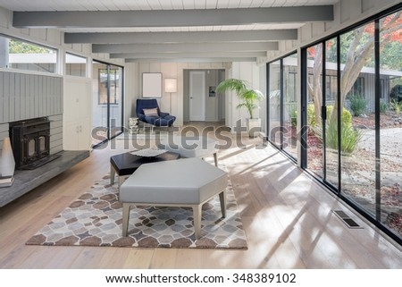 Modern living room interior in mid century home with couch, fire place, hand-woven natural fine sisal rug, glass table, designer chairs in open space. - stock photo