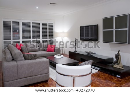 modern living room interior with charcoal sofa and chocolate brown coffee table and wide screen plasma TV.