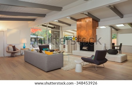 Modern living room interior with designer furniture, grey couch, fire place, hand-woven natural fine sisal rug, glass table, designer chairs in open space. - stock photo