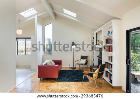 Modern living room interior with peak roof and sliding door leading to outdoors. Living room with bookcase chairs and reading lamp.  - stock photo
