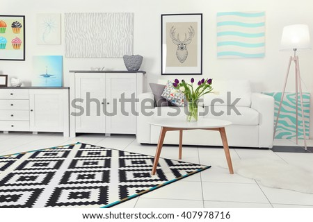 Modern living room interior with white sofa, coffee table, big graphic carpet and canvases on the white wall