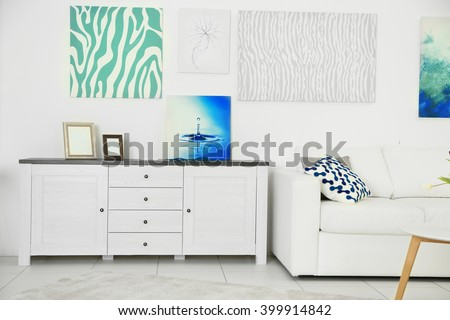 Modern living room interior with white sofa, lockers and canvases on the white wall - stock photo