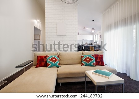 Modern living room sofa and coffee table with kitchen in background - stock photo