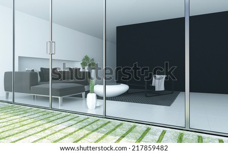 Modern living room viewed from a patio through a floor to ceiling glass wall or windows with an upholstered lounge suite and minimalist grey and white decor - stock photo