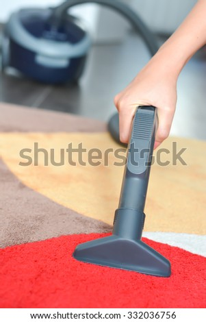 Modern living room, with a vacuum cleaner to tidy up - stock photo