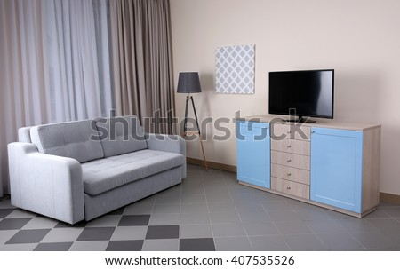 Modern living room with couch and TV. - stock photo