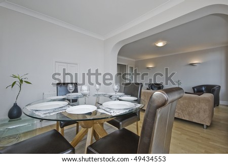 modern living room with glass top dining table - stock photo