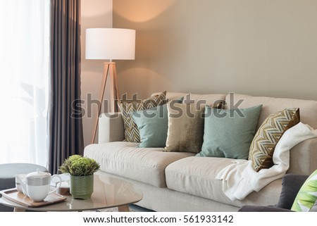Modern Living Room With Green Pillows On Cozy Sofa And Wooden Lamp,  Interior Design