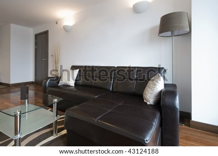 modern living room with large leather corner sofa and a glass coffee table