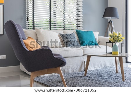 modern living room with modern chair and sofa with vase of plants at home - stock photo