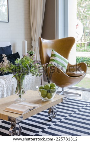 modern living room with plant in vase on wooden table - stock photo