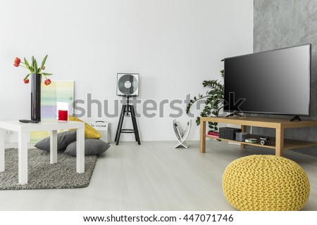Modern living room with simple but trendy furniture and a tv set, arranged in grey and yellow - stock photo