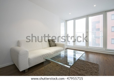Modern living room with white leather two seater sofa and glass coffee table - stock photo