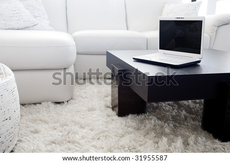 Modern livingroom. White furniture - sofa and couch with a laptop on table