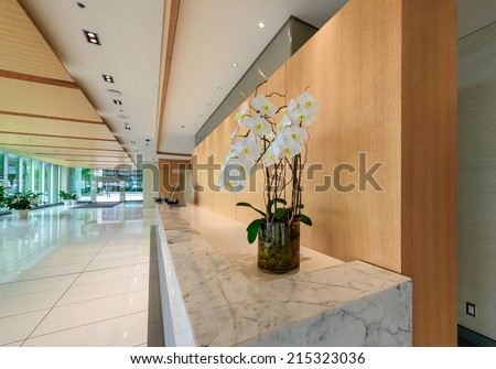 Modern lobby, hallway with marble counter with some flowers on it,  of the luxury hotel, business center, shopping mall in Vancouver, Canada. Interior design. - stock photo