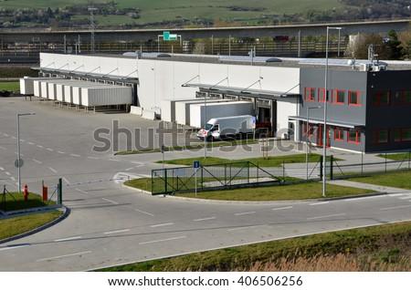 Modern logistics center, white van and trailers standingon ramp - stock photo
