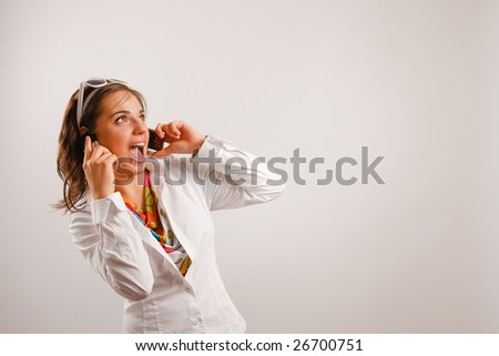 Modern looking young woman wearing white jacket talking on the phone - stock photo