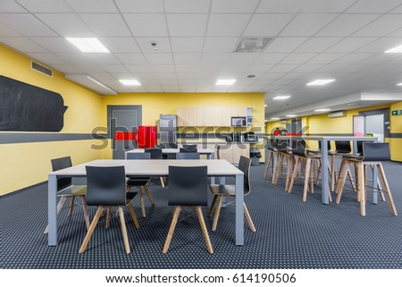 Modern Lunchroom Interior With Wooden Tables And Black Chairs, Kitchenette  In Background