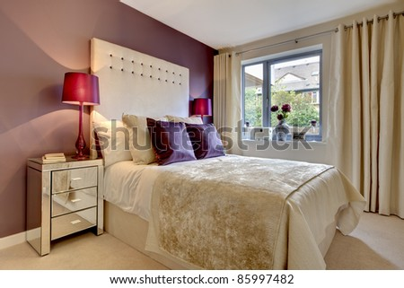 Modern luxury bedroom stylishly dressed with fashionable brightly coloured fabrics - stock photo