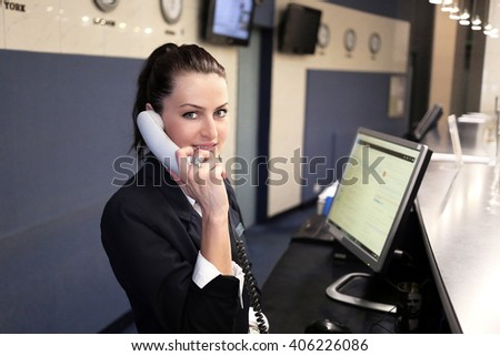 Modern luxury hotel reception counter desk with bell. Two happy females receptionist worker standing at hotel counter. - stock photo