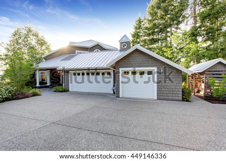 Modern luxury house exterior with curb appeal. View of garage with  driveway and small porch with white columns