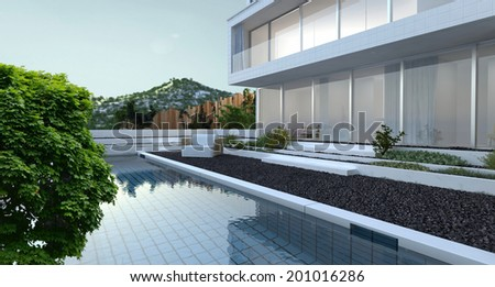 Modern luxury house with panoramic view windows overlooking a patio laid to pebbles with swimming pool and a mountain peak in the background - stock photo