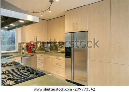 Modern luxury kitchen in light wood with all new stainless steel appliances with espresso machine and red grinder.  - stock photo